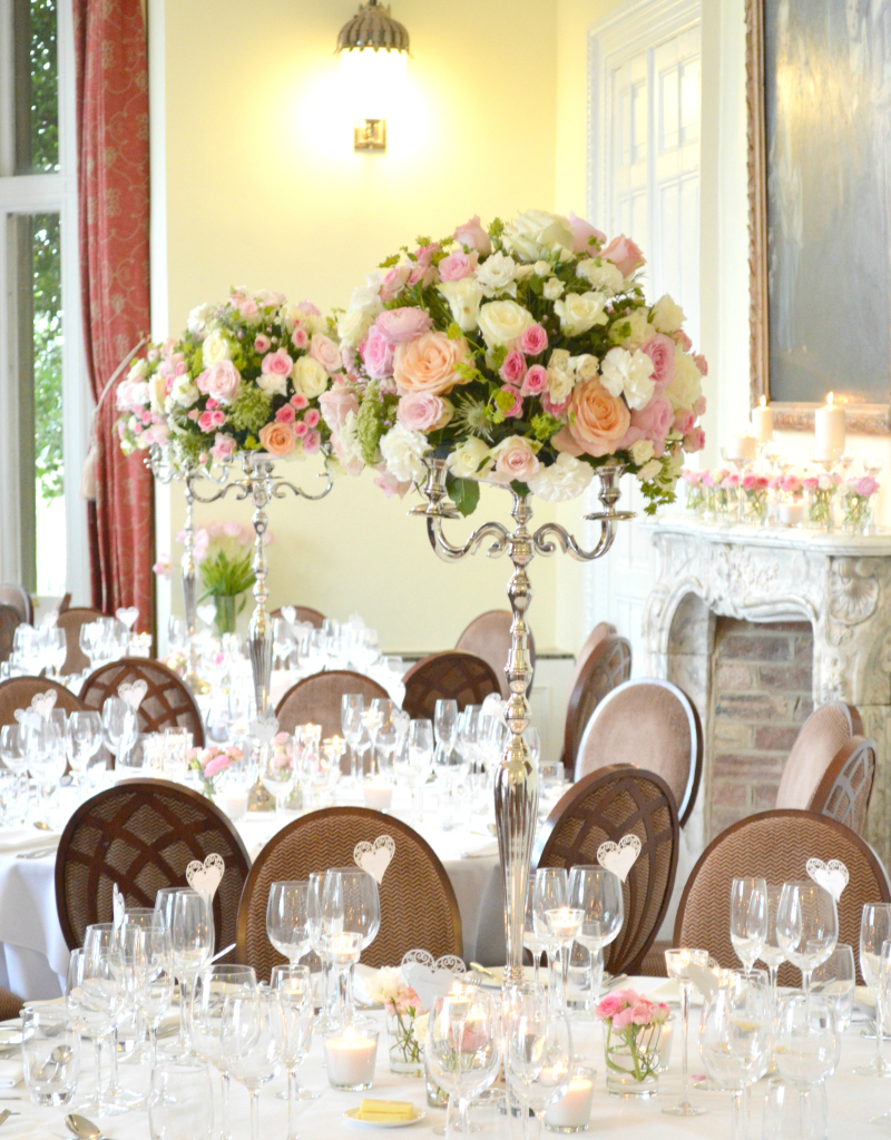 Cherie Kelly Fawsley Hall Wedding reception guests table candelabra flower arrangements tall and low centrepieces fireplace with candles