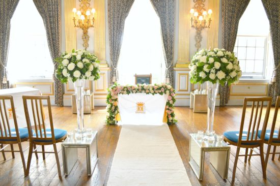 Wedding aisle white roses and green flower tall vase arrangements and registrar flower garland Cherie Kelly Knowsley Hall