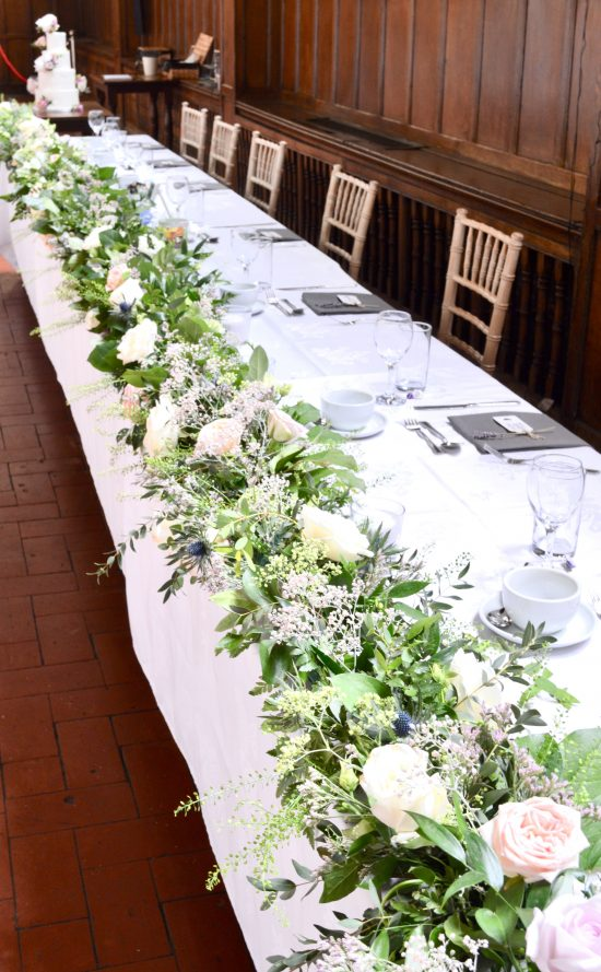 Rustic pink and blue Roses, Thistle, Lisianthus, Peonies, David Austin roses, Delphinium and foliage headtable garland wedding Cherie Kelly flowers London