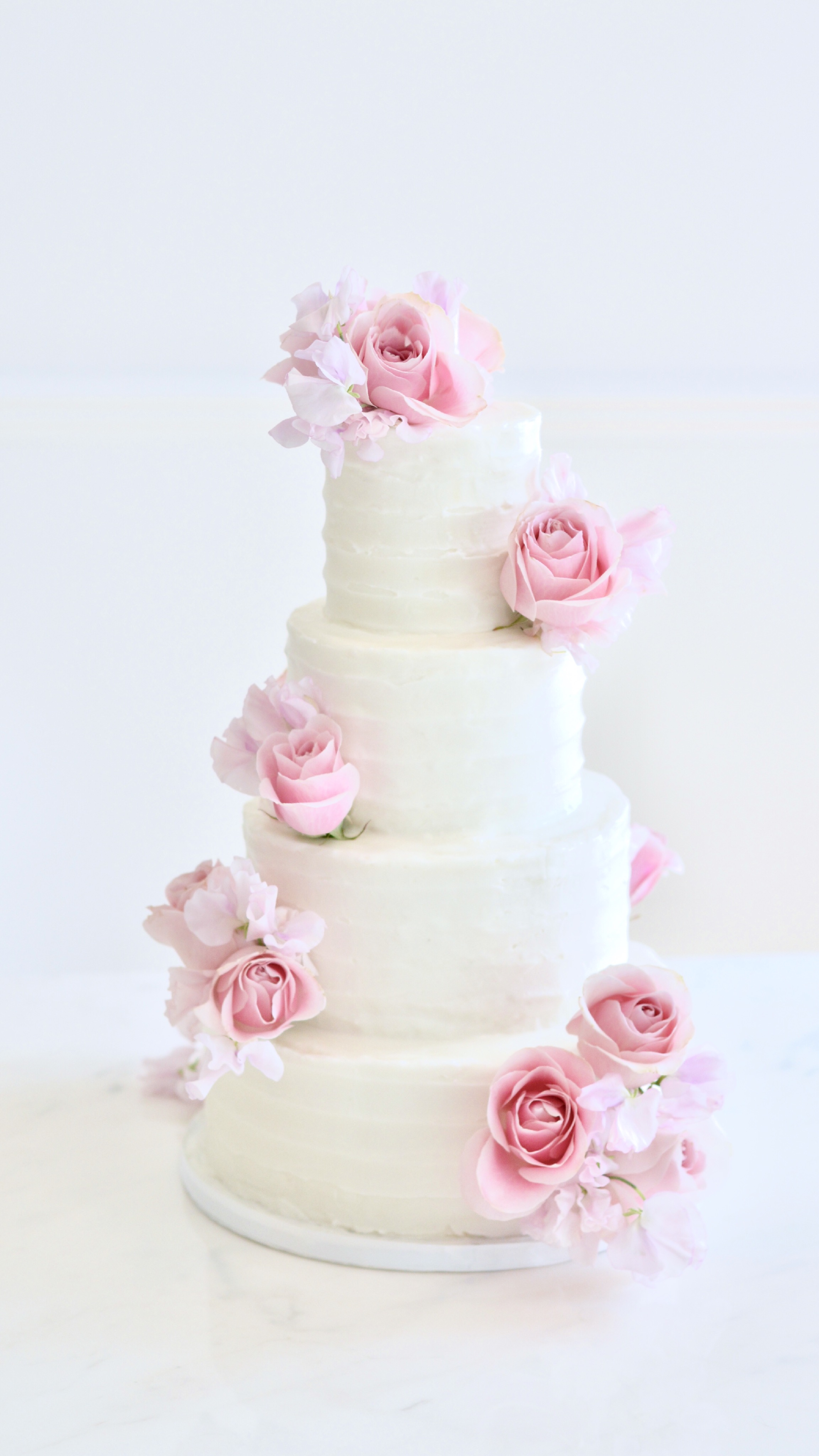4 tier buttercream rustic wedding cake with pink roses and sweet pea Cherie Kelly London