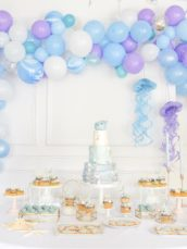 Under the sea themed birthday party cake dessert table cookies mermaid cakepops cupcakes balloon garland arch Cherie Kelly cakes London