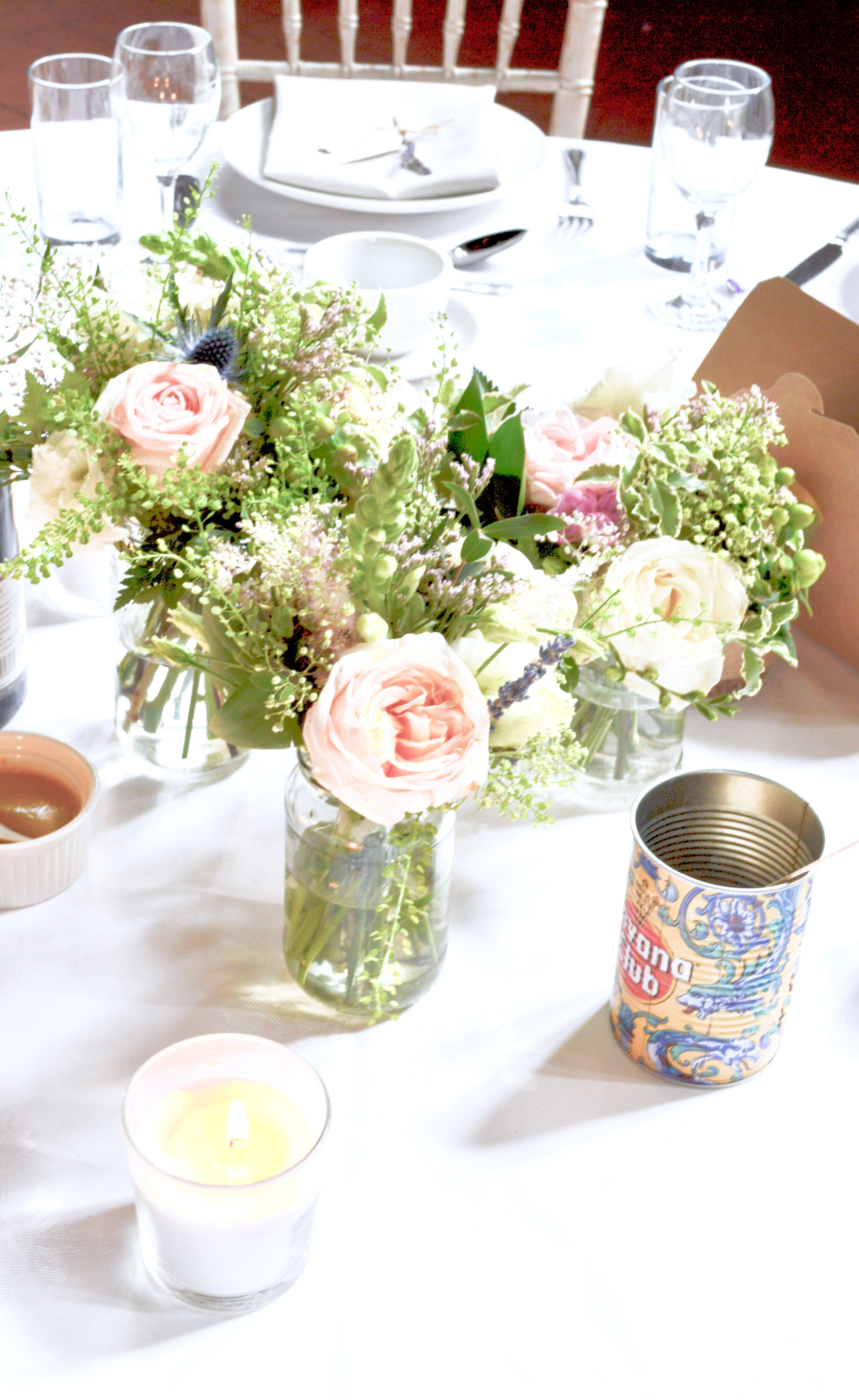 Rustic pink and blue Roses, Thistle, Lisianthus, Peonies, David Austin roses, Delphinium and foliage wedding centrepieces jam jars Cherie Kelly flowers London